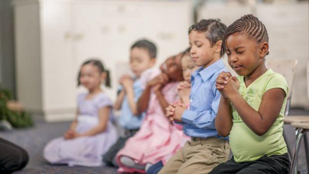 Crianças rezando em sala de aula