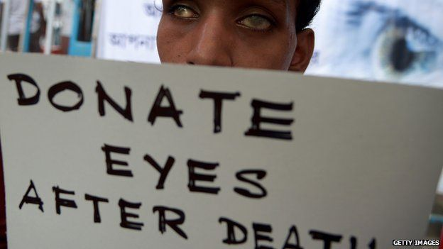 An Indian visually challenged youth holds a poster during a campaign to create awareness about eye donation in Kolkata on August 27, 2014.