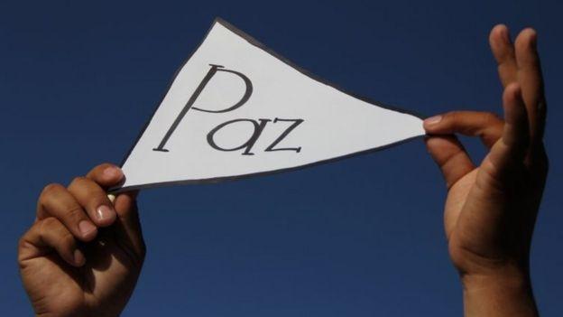 """Una persona sostiene un cartel con la palabra """"Paz"""""""