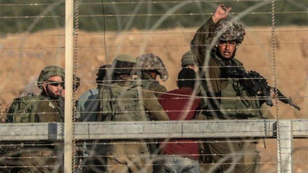 Los soldados israelíes detienen a un palestino.