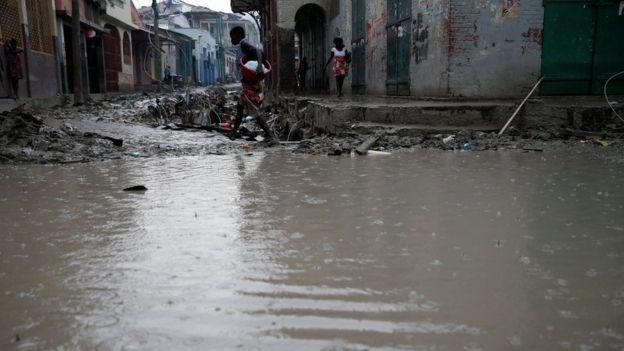 People walk in a flooded street after Hurricane Matthew hit Jeremie