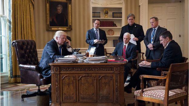 Donald Trump hablando por teléfono con Vladimir Putin en el Despacho Oval en enero de 28, 2017 en Washington, DC. De izquierda a derecha, el ex jefe de gabinete de la Casa Blanca, Reince Priebus; el vicepresidente Mike Pence; el ex jefe de estrategia de la Casa Blanca, Steve Bannon; el ex secretario de prensa Sean Spicer y el ex asesor de seguridad nacional Michael Flynn.