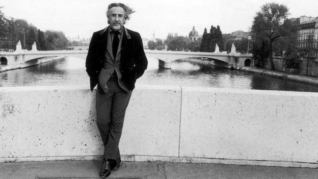 Imagen del escritor sobre un puente, con el agua de fondo.