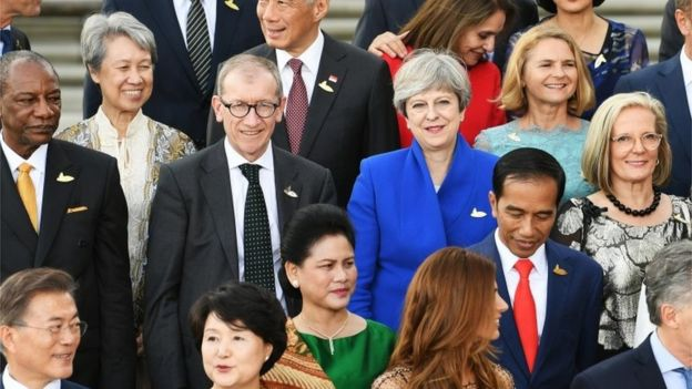Theresa May and her husband Philip May during a group photograph as G20 leaders and their spouses arrive to attend a concert