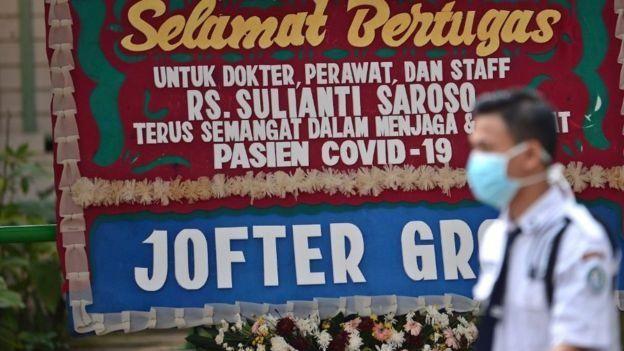 Petugas berjalan di samping karangan bunga dukungan untuk tenaga medis dan staf Rumah Sakit Penyakit Infeksi (RSPI) Sulianti Saroso di Jakarta, (21/3).