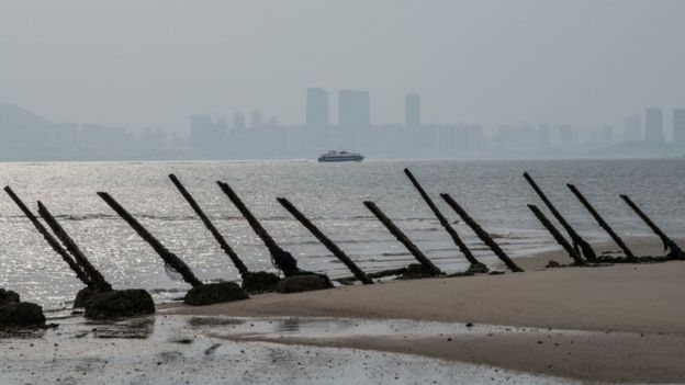 The Chinese city of Xamen is seen in the distance behind aged anti-landing barricades on a beach facing China on the Taiwanese island of Kinmen which, at points lies only a few miles from China, on April 19, 2018 in Kinmen, Taiwan.