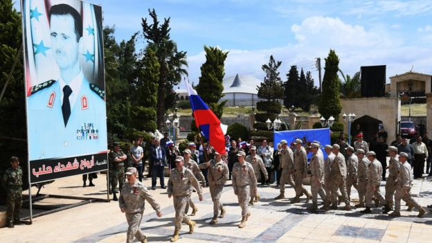 Russian soldiers parade in front of a poster of Syrian president Bashar al-Asad during a ceremony marking Soviet victory over Nazi Germany in WW II, in Aleppo's Saadallah al-Jabiri square in northern Syria on May 9, 2018.