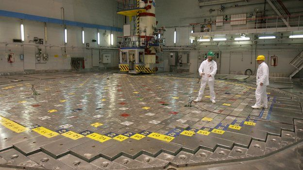 Technicians stand opposite a nuclear reactor head at the Ignalina nuclear power plant in Visaginas, Lithuania, on December 18, 2009.