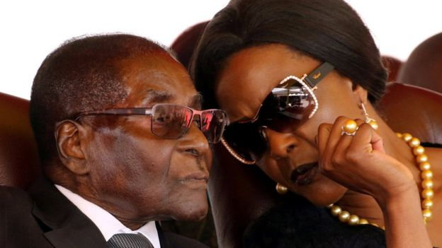 President Robert Mugabe (L) and his wife Grace are pictured speaking closely during a funeral they attended in August