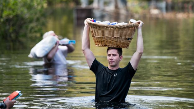 Hombre caminando en el agua en Southport, Carolina del Norte, con una cesto en la cabeza