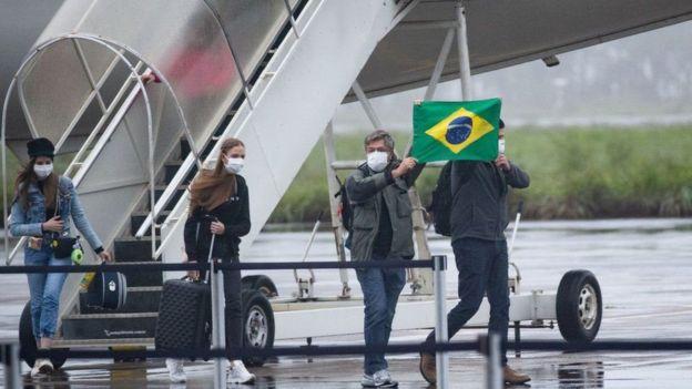 Personas con mascarilla y una bandera de Brasil.