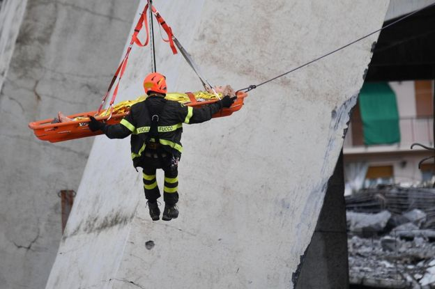 Rescuers recover an injured person after a highway bridge collapsed in Genoa, Italy, 14 August 2018