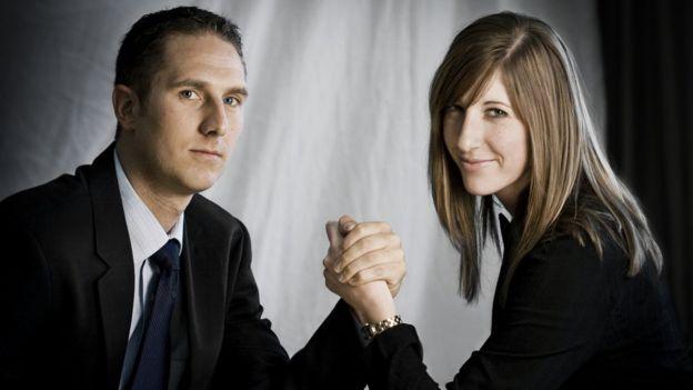 Homem em mulher fazendo queda de braço