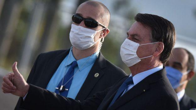 Usando uma máscara protetora, o presidente do Brasil, Jair Bolsonaro, chega à cerimônia de Levantamento da Bandeira Nacional em frente ao Palácio da Alvorada em meio à pandemia de Coronavírus (COVID-19), em Brasília, Brasil, na terça-feira, 9 de junho de 2020