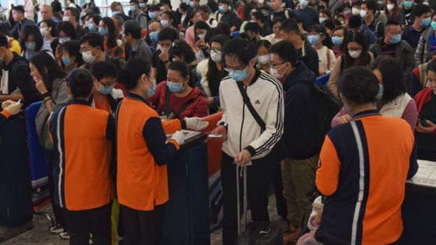People with masks queuing at Hong Kong's airport