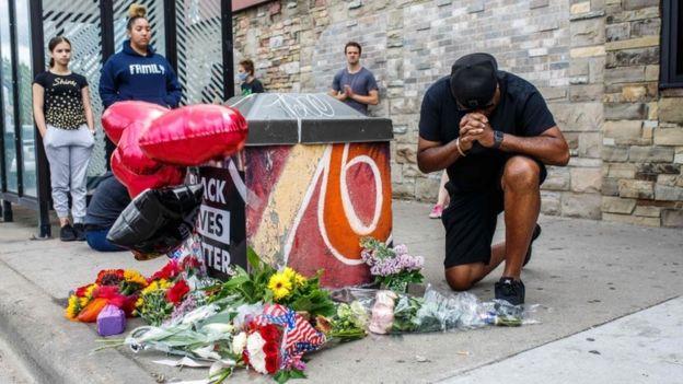 Un manifestant prie devant un mémorial pour George Floyd, dont la mort a relancé le débat sur la brutalité policière aux États-Unis