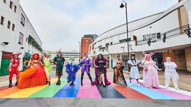 Drag artists standing on rainbow crossing