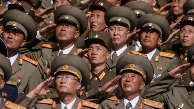 Korean People's Army (KPA) soldiers salute as they watch a mass rally on Kim Il Sung square in Pyongyang on September 9, 2018
