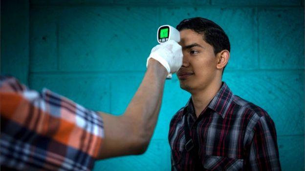 Funcionario toma la temperatura de un hombre en Nicaragua