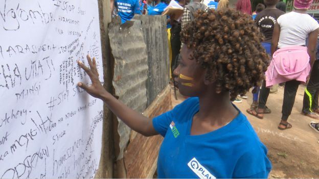 A photo of a young woman in Kibera looking at some of the street harassment messages that were written on canvas by others