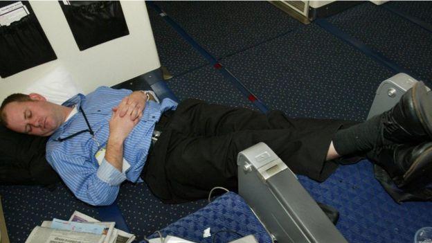 Un pasajero dormido en el pasillo de un avión