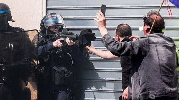 Policía apuntando con una pistola de balas de goma a un manisfestante