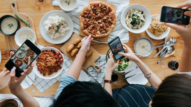 Gente sacándole foto a sus comidas