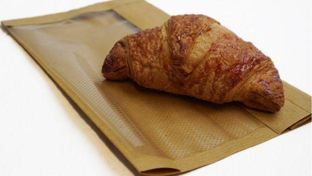 Um Croissant em um saco de padaria com a alternativa para plástico em cima