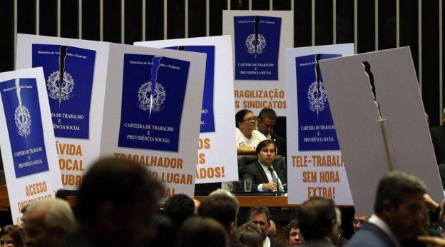Manifestantes contra a reforma trabalhista empunham cartazes no plenário da Câmara dos Deputados