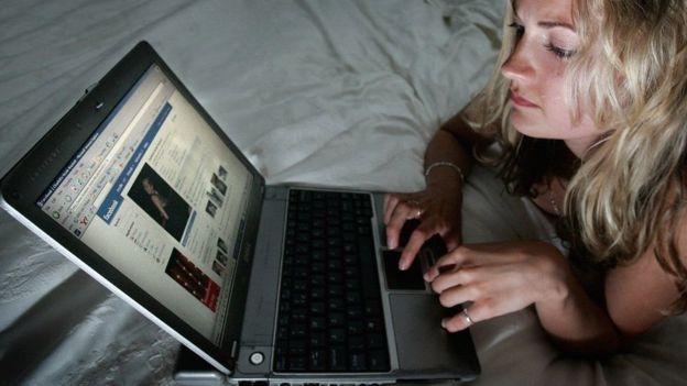 Mujer ve Facebook en su computadora portátil.