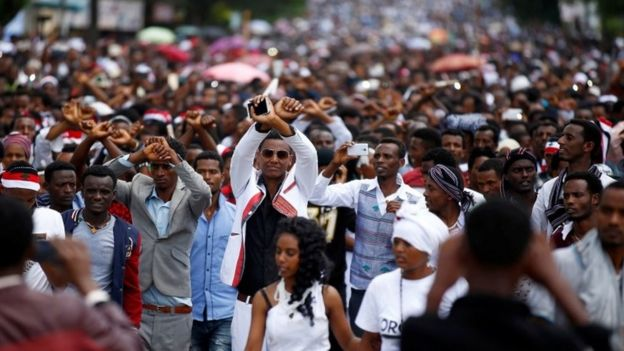 Demonstrators show the Oromo protest gesture sign during Irreecha, the thanks giving festival of the Oromo people in Bishoftu town of Oromia region, Ethiopia, October 2