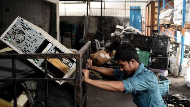 Hombre en fábrica de reciclaje electrónico.