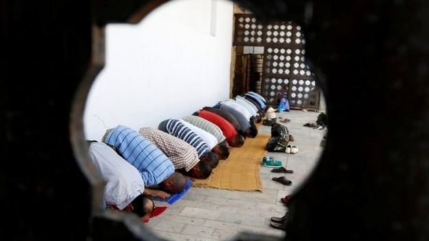 Men praying at a mosque in Tunis