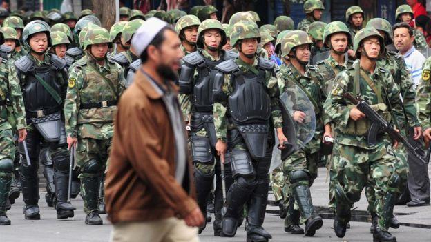 أحد مسلمي الويغور يمر امام فرقة من الجيش الصيني في أورومكي عاصمة إقليم تشنغيانغ