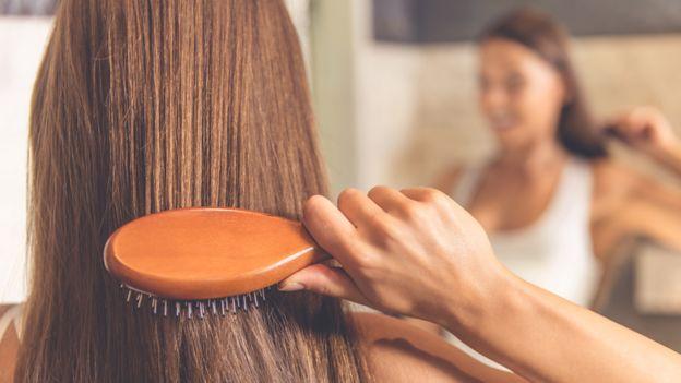 Una mujer se cepilla el pelo de espaldas