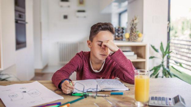 Menino demonstrando frustração ao estudar