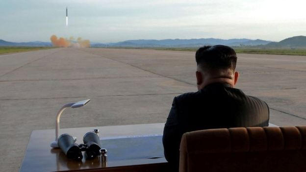 North Korean leader Kim Jong-un watches the launch of a Hwasong-12 missile in this undated