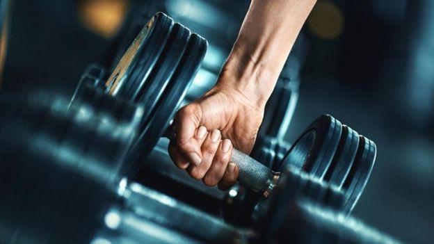 Mão humana puxando alteres de exercício
