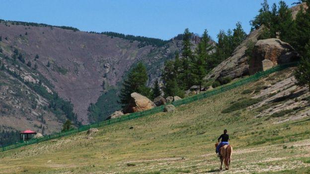 Una persona a caballo en las montañas mongolesas