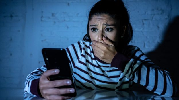 Stock image of a woman looking at her phone in shock.