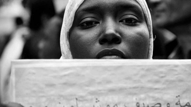 فتاة سمراء تحمل لافتة ضد العنصرية