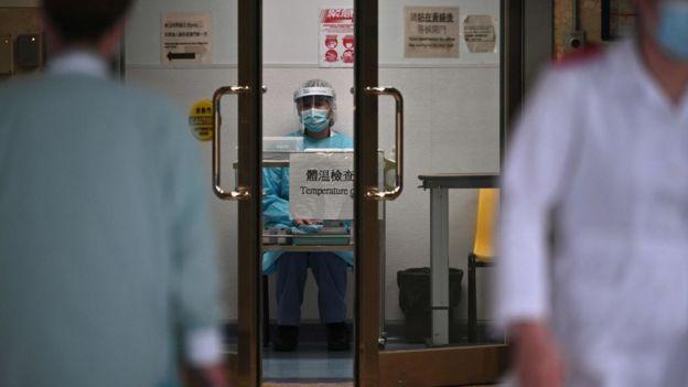 Hong Kong'daki Prenses Margaret Hastanesi'ndeki bir sağlık görevlisi hastaneye gelenlerin sıcaklıklarını ölçmek için bekliyor