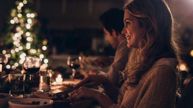 Mujer sonriendo durante la cena de Navidad.