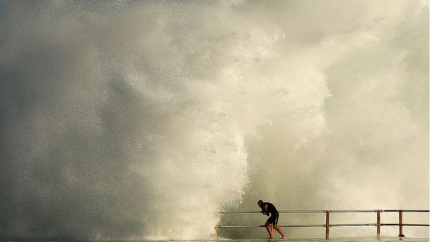 Man grabs onto railing as huge wave splashes against ocean pool