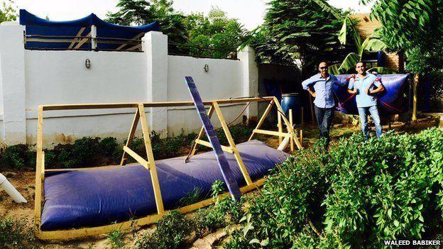 Khartoum franchise owner Waleed Babiker (left) stands next to his digester in Khartoum
