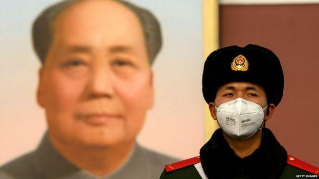 Поліцейський охороняє портрет Мао Цзедуна