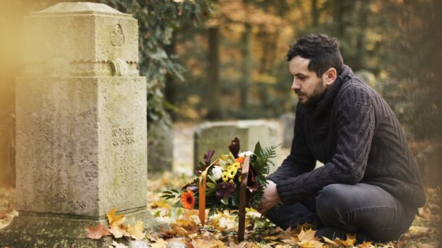Man with flowers next to grave