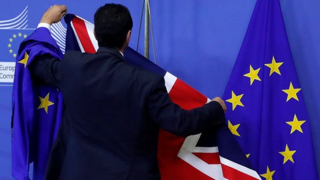 EU official hanging a Union Jack flag next to an EU flag