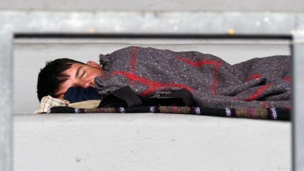 Un niño migrante duerme en el estadio en Ciudad de México
