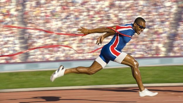 African-American sprinter crossing the finish line and breaking the tape